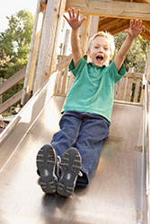 photo of boy on a slide